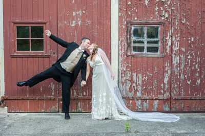 Bride and groom holding hands and kissing.