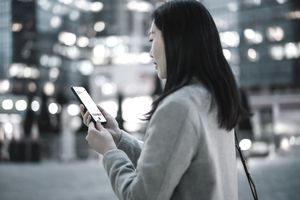 Young Asian businesswoman checking financial stock market analysis with mobile app on smartphone on the go, against illuminated contemporary corporate skyscrapers in financial district in the evening.