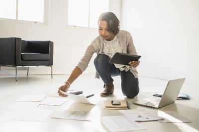 Businesswoman using laptop and digital tablet while kneeling on floor