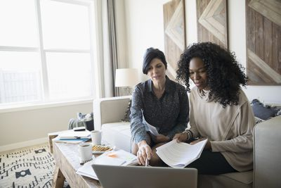 Financial advisor with laptop and paperwork meeting with woman in living room
