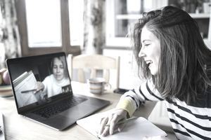 A college coach advises a student via video conference.