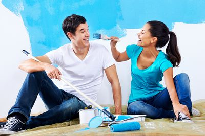 A young couple painting their home to get ready to sell it