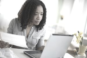 Mixed race woman paying bills online