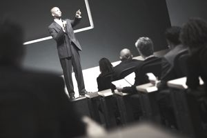 Man in suit on stage calls on a shareholder at a shareholder meeting