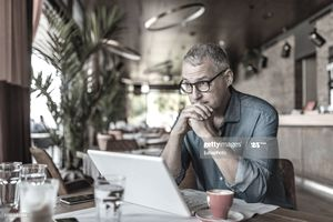 Man seated at a cafe table with laptop, looking thoughtful