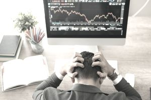 Day trader sitting at a desk with a stock market chart holding his head and feeling frustrated after losing money.