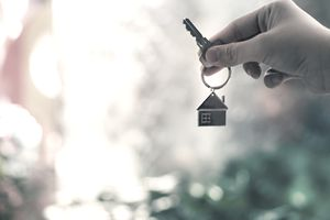 Hand holding a key with a house-shaped keychain charm, representing applying for a home loan.