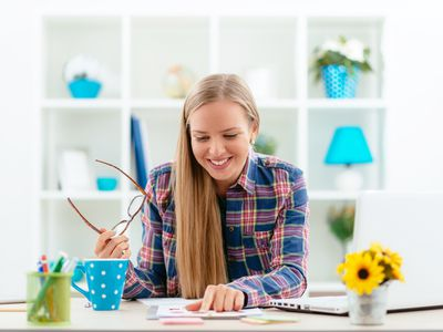 Young businesswoman at a home desk with laptop and paperwork