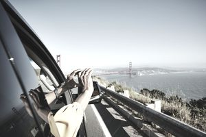 Woman taking photo of Golden Gate Bridge out of car window with smartphone