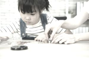 little girl in overalls looking at coins