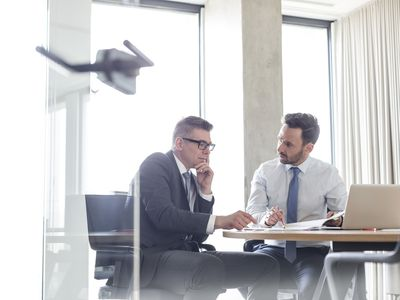 Two men discussing contract in office