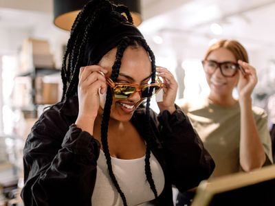 Two women try on glasses.