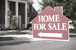 Close-up of a sign pointing to a home for sale in suburbia