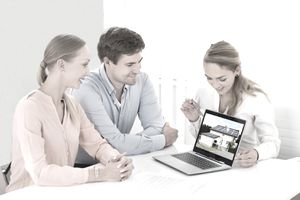 Agent and couple looking at a picture of a house on a laptop
