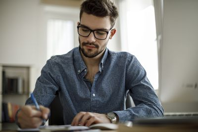 Man in blue shirt calculating something on his desk