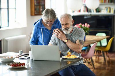 Senior man at breakfast bar eating scrambled eggs, woman with hand on his shoulder looking at laptop, couple doing home finances over breakfast