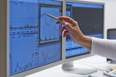 a woman pointing to a graph on a computer monitor