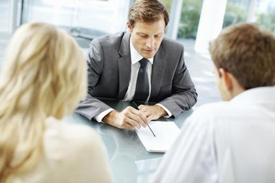 a businessman conversing with a couple
