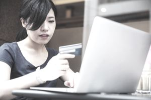 Young Japanese woman using her credit card to do online shopping