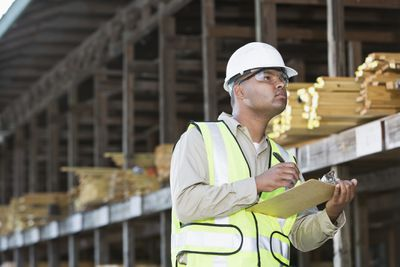 A man in a reflective vest, goggles and helmet takes inventory in a lumber yard.