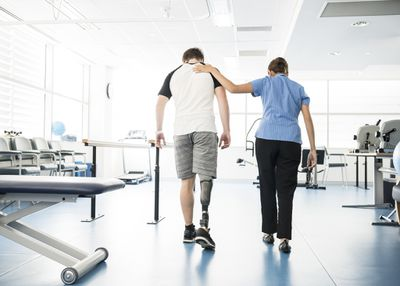 A young man walks across a gym on a new prosthetic leg with the help of a physical therapist