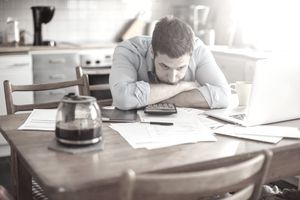 A man looking distressed with paperwork and a pot of coffee
