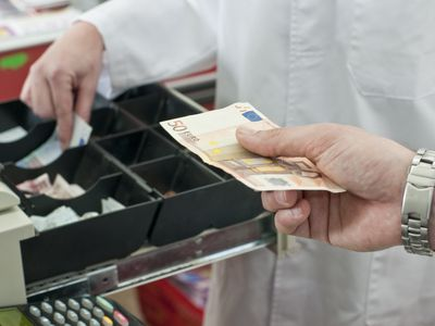 cash in hand of customer paying in supermarket