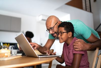 A father and son look at a computer.