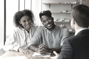 Smiling biracial man and woman talk with male real estate agent at office meeting.