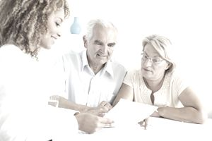 Elderly couple looking over living trust documents with an estate planning attorney