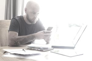 A man works out debt forgiveness with a laptop, a smartphone, and a pile of papers.