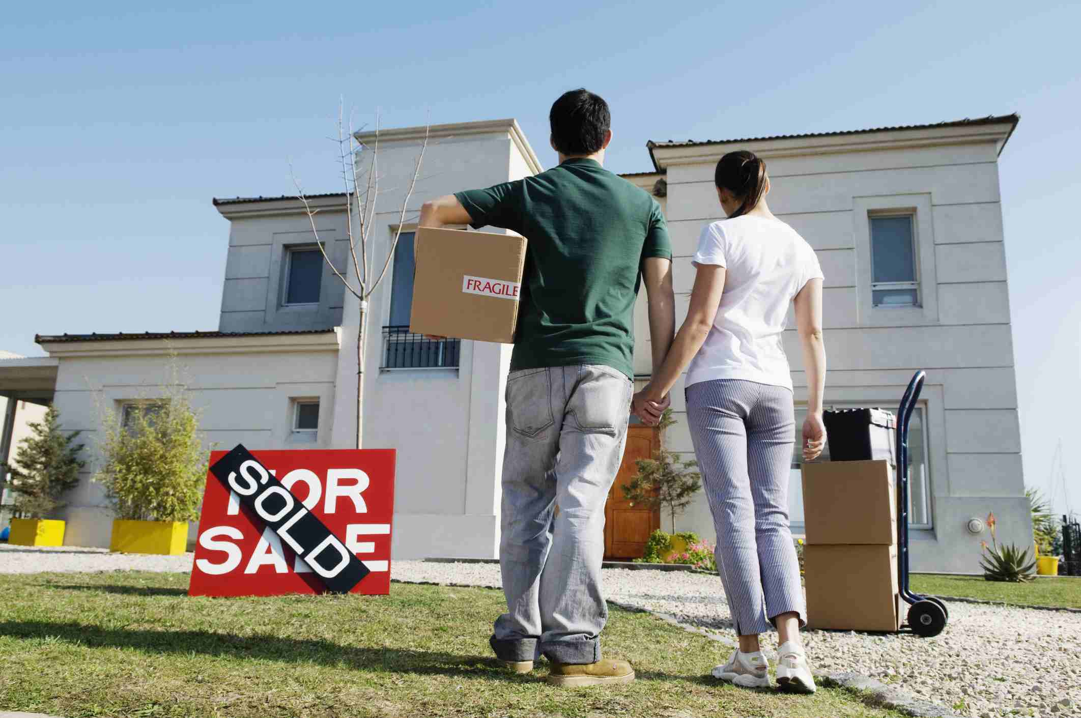 a young couple looking at their new house near the for sale sign with