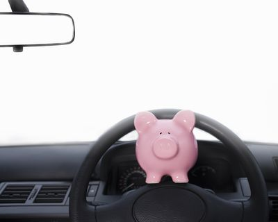 Piggy bank perched on the steering wheel of a car to reflect there are ways to save money in driving