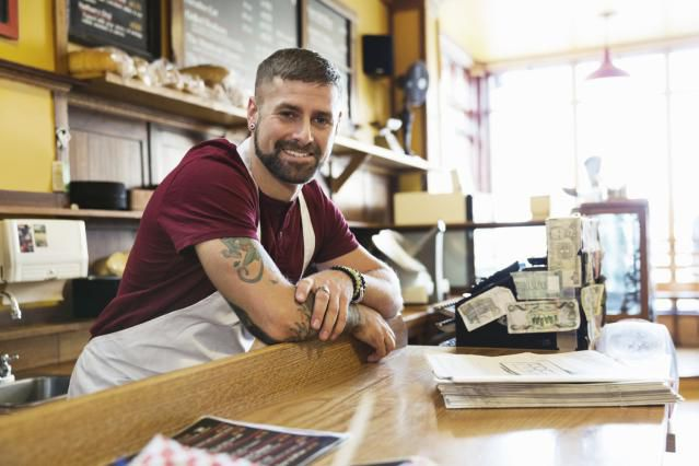 Business owner standing near the cash register and leaning on the service counter