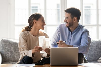 Couple sitting on sofa discussing money and budget