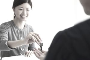 Woman handing keys over to someone with a smile