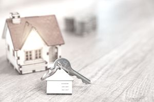 House key on a house shaped keychain resting on table