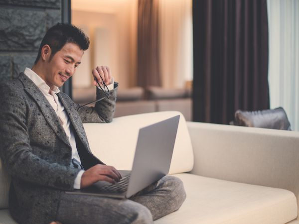 Man on couch working on laptop