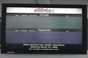 An airport info screen displays no arrivals nor departures for bankrupt airline Aloha Airlines.