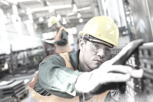 Focused worker examining steel part in factory