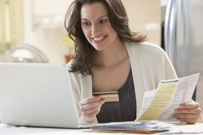 Woman responsibly paying bills, which is one of the best ways to build credit