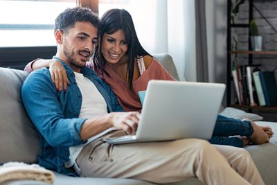 Couple sitting on couch using laptop