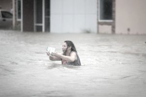 Woman in a flooded street during Hurricane Harvey in Houston, Texas