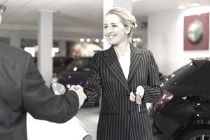 Young woman buying her first car, smiling and shaking hands with the salesperson in the dealer's showroom.