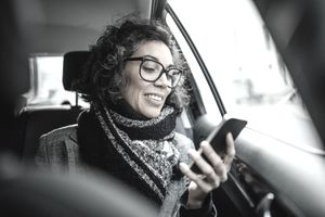 Middle-aged woman checking prices on phone in car