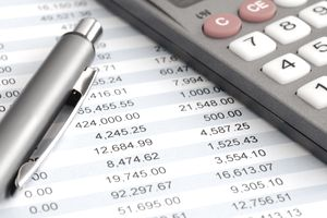 Pen and calculator on top of balance sheet