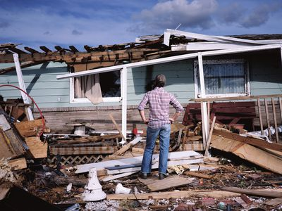A man stands in front of a destroyed house, hands on his hips.