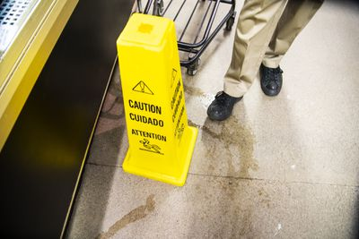 A customer about to step into a puddle of water in a supermarket