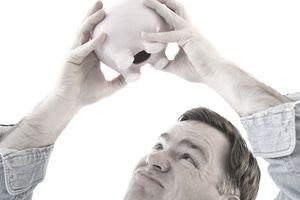 a frustrated man shakes an empty piggy bank