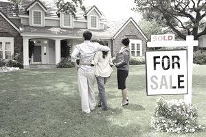 "Realtor standing with couple in front of a house with a ""For Sale"" sign"